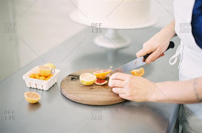 Baker slicing blood oranges