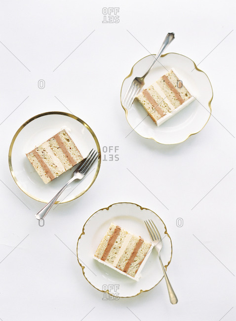 Three plates of wedding cake with layers of chocolate and vanilla buttercream
