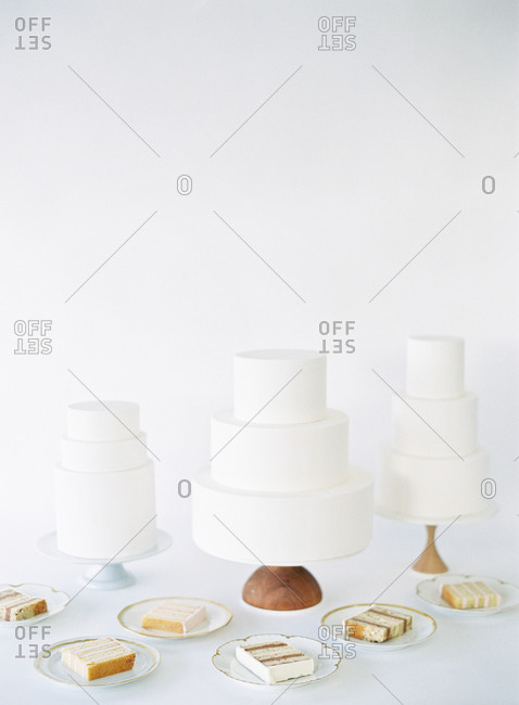 Three simple white three tier cakes with slices on plates