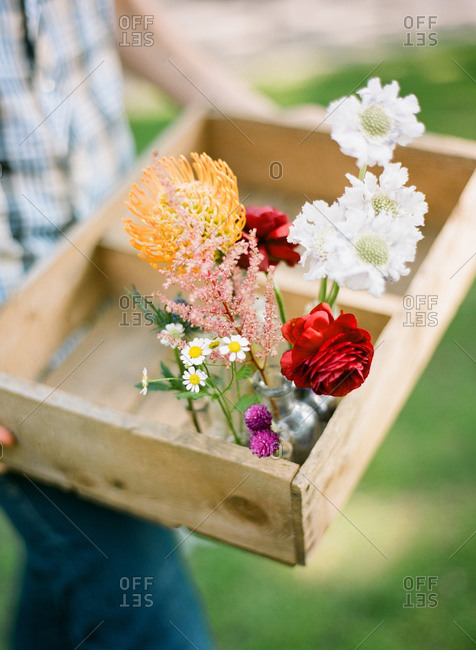 Man carrying a few flowers in a wood crate