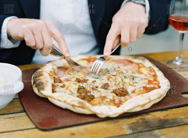 Man cutting his pizza with a fork and knife