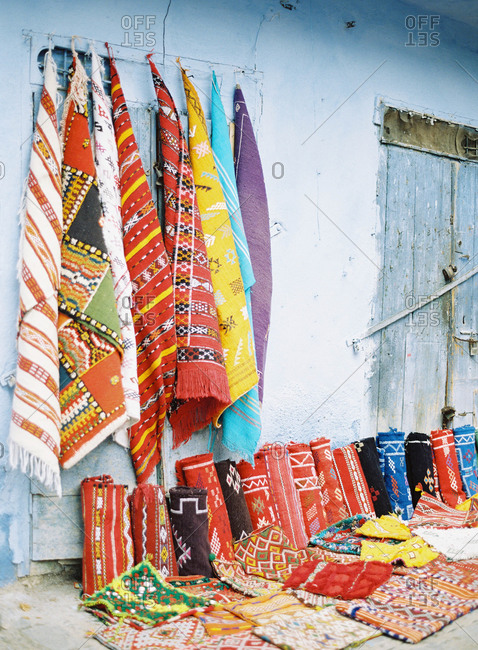 Woven textiles hanging and lined up against an exterior wall