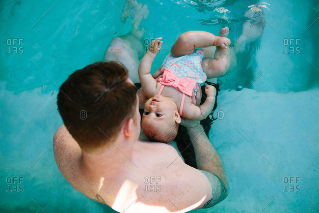 Father teaching his baby daughter how to float