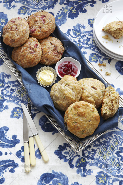 Biscuits with butter and jam on blue floral tablecloth