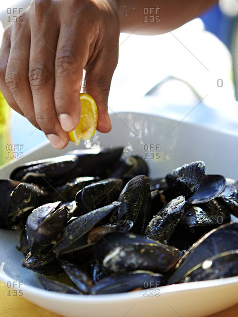 Hand squeezing lemon over cooked mussels