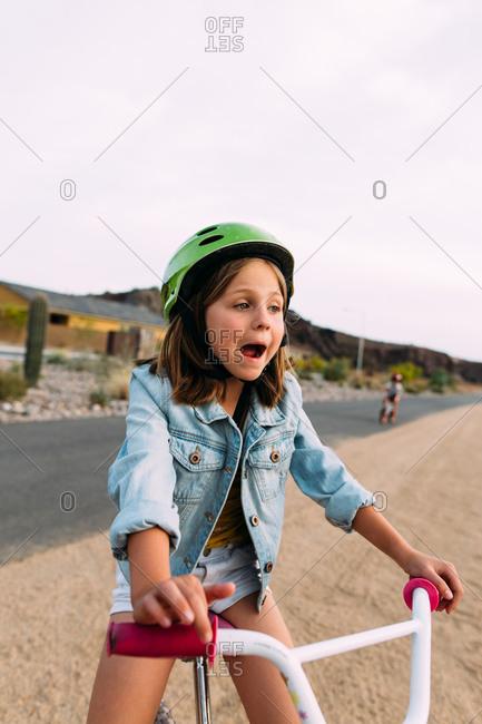 Girl riding her bike playfully looking shocked