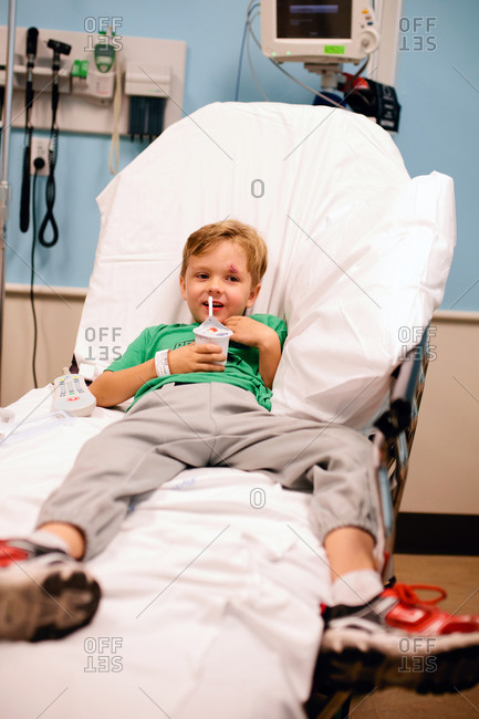 Boy lying in a hospital bed and eating a snack
