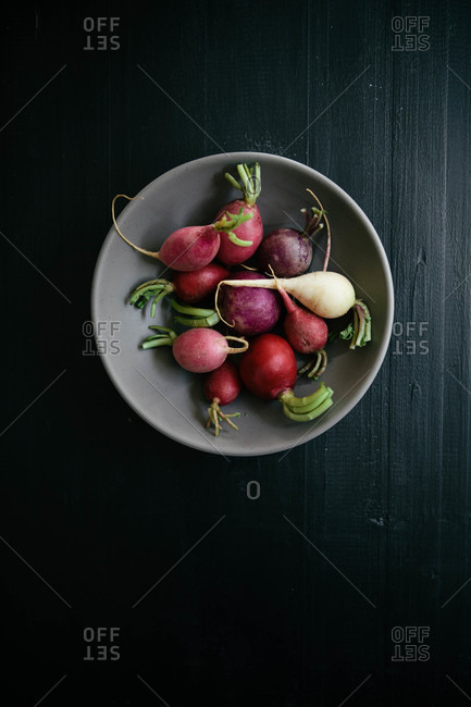 Various colored radishes in a ceramic bowl