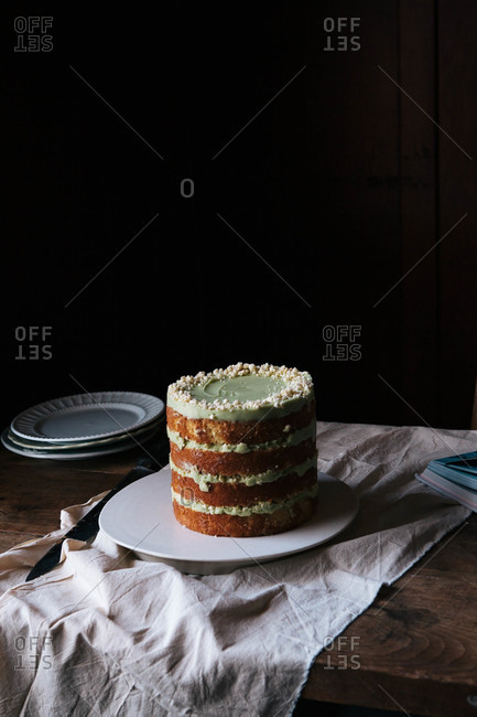 Layered cake with green frosting and crumbles on top
