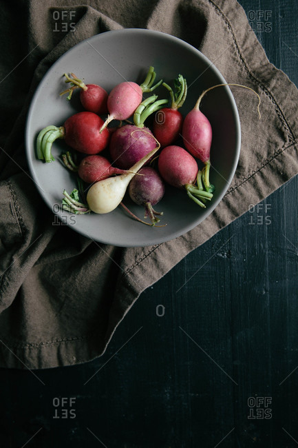 Various colored radishes in a ceramic bowl on a cloth napkin