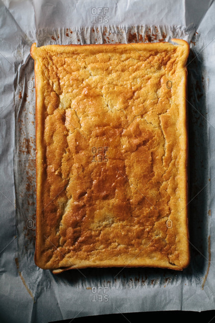 Golden sheet cake resting on parchment paper