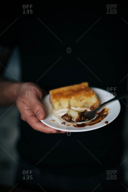 Man holding a plate with a piece of golden cake and chocolate sauce
