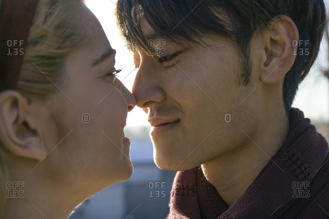 Young man touching nose of his girlfriend with his nose