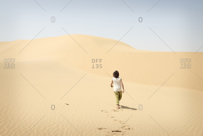 Barefoot man walking alone in the desert