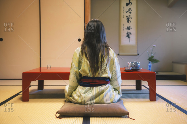 Back view of woman wearing yukata drinking tea in a traditional Japanese room