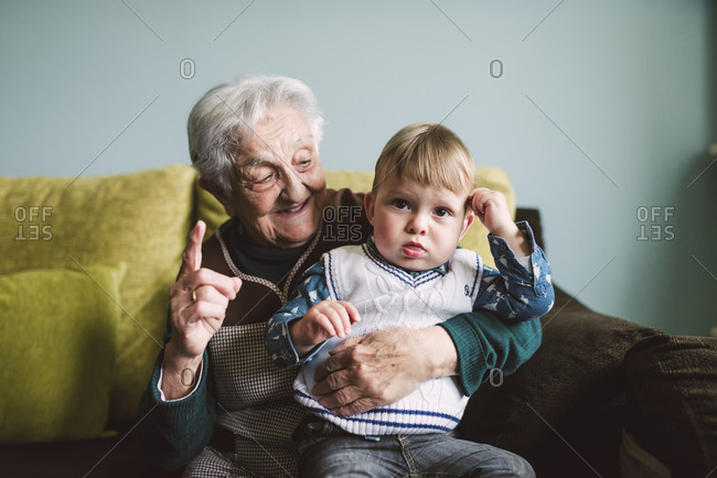 Elderly woman and her great-grandson sitting on the couch