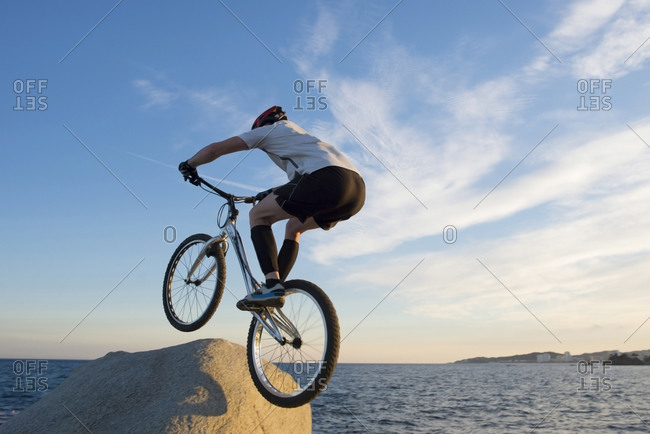 Bmx rider jumping on a rock in the evening