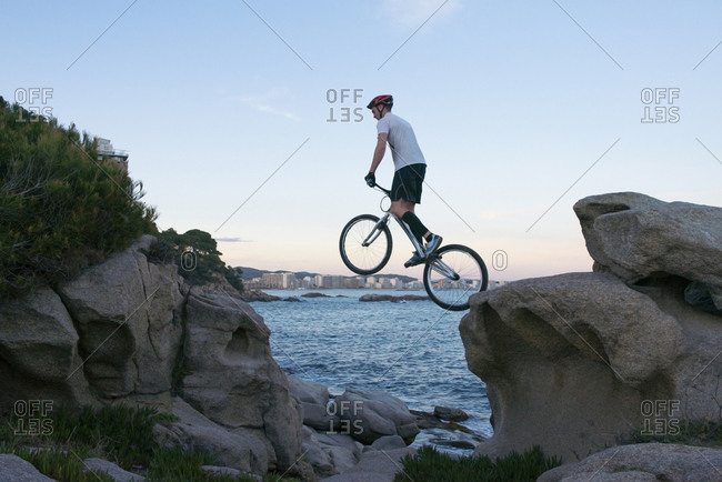 Bmx rider jumping from rock to  rock in the evening