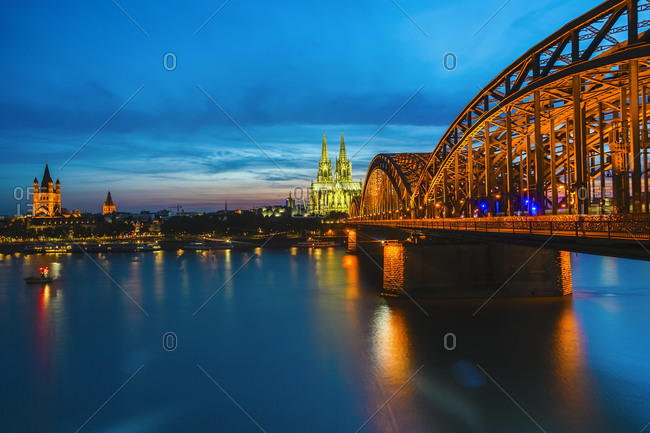 View to lighted Cologne Cathedral with Hohenzollern Bridge in the foreground