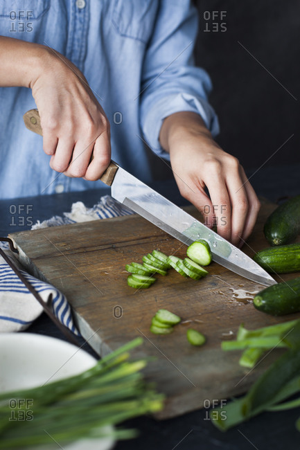 Chef slicing cucumbers on wooden cutting board