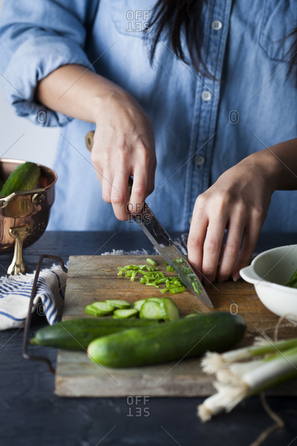 Hands slicing chives on wooden cutting board with cucumbers and green onions