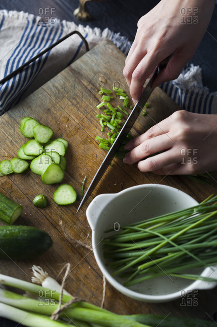 Overhead view of person slicing chives on wooden cutting board