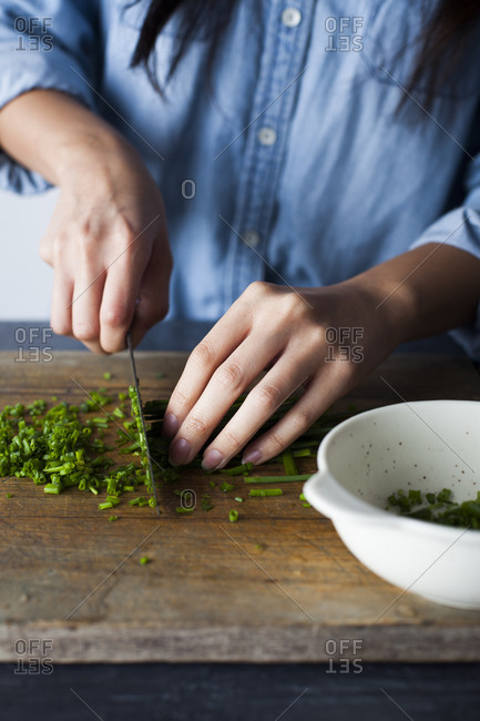 Person's hands slicing fresh chives on wooden cutting board
