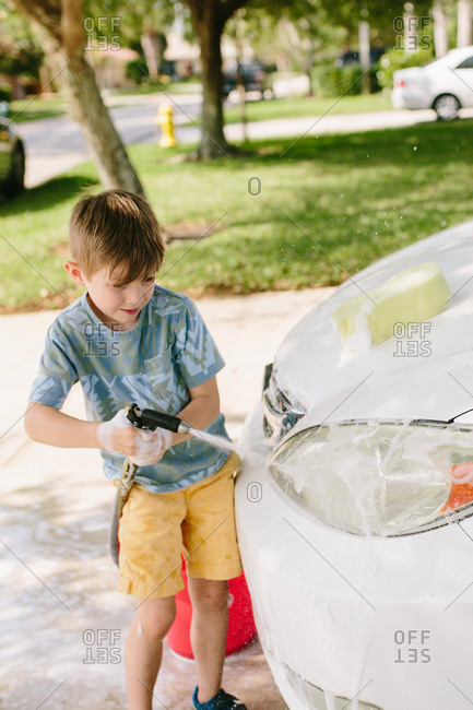 Boy washing a car in the driveway