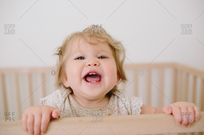 Toddler looking over the railing of her crib