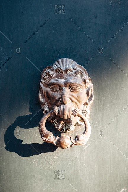 Ornate antique brass door knocker on a door in Aix-en-Provence, France