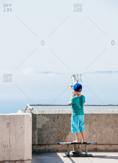 Boy looking through a sightseeing telescope