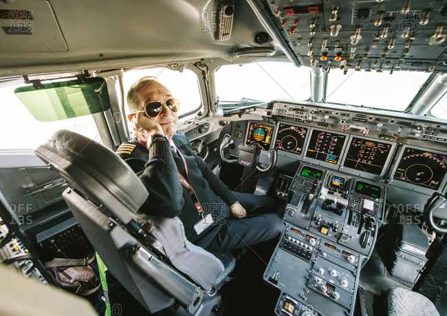Strasbourg, France - March 20, 2016: Portrait of male pilot wearing aviator sunglasses in airplane cockpit