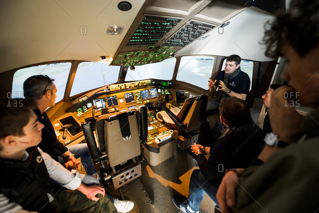 Strasbourg, France - March 20, 2016: Instructor explaining to future pilots the principles of piloting an Being 777 at the Flight Simulation Center with the exact replica of the Boeing 777 cockpit flight simulator