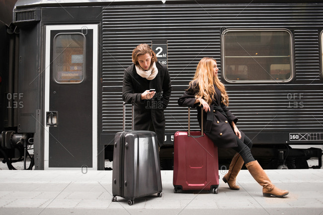 Couple leaning against rolling luggage in a train station