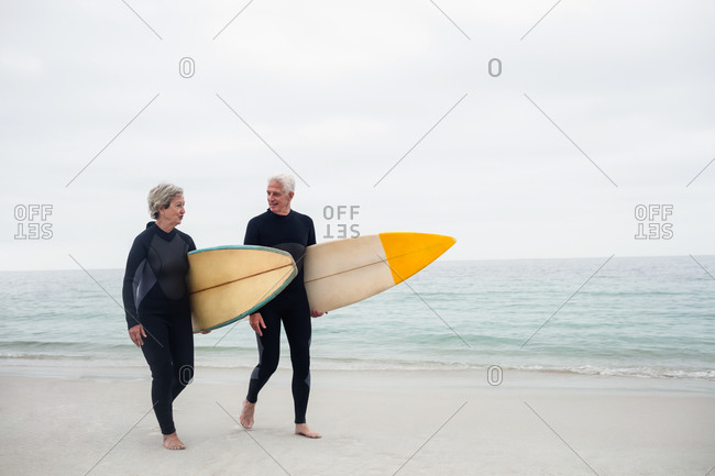 Senior couple with surfboard walking on the beach on a sunny day