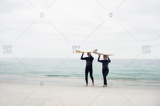 Senior couple in wetsuit carrying surfboard over head on the beach