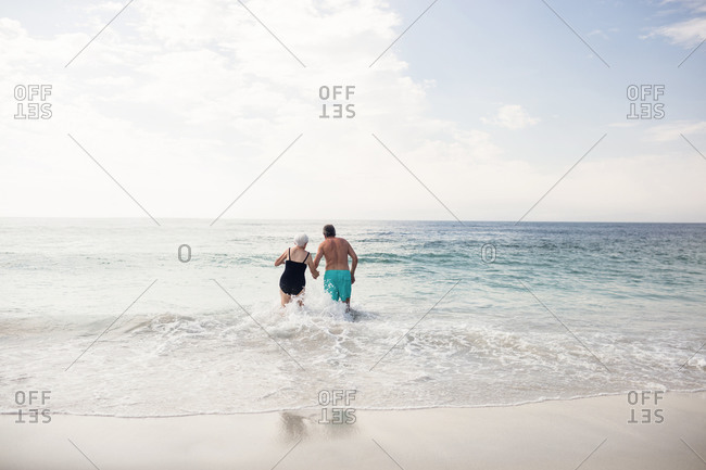 Rear view of senior couple holding hands and walking in sea on a sunny day