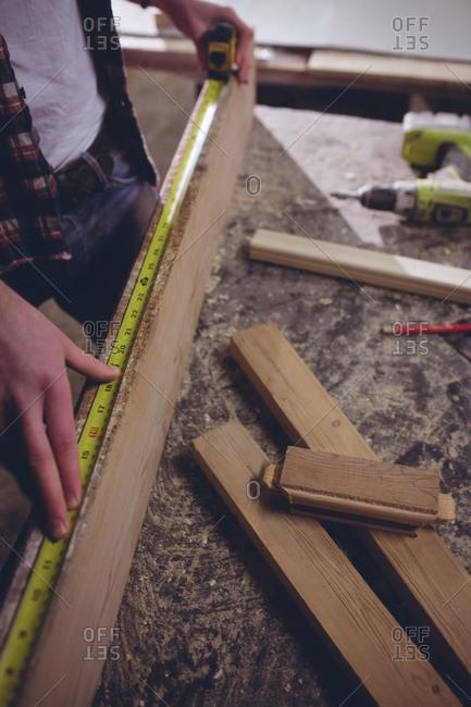 Carpenter using measuring tape on wood
