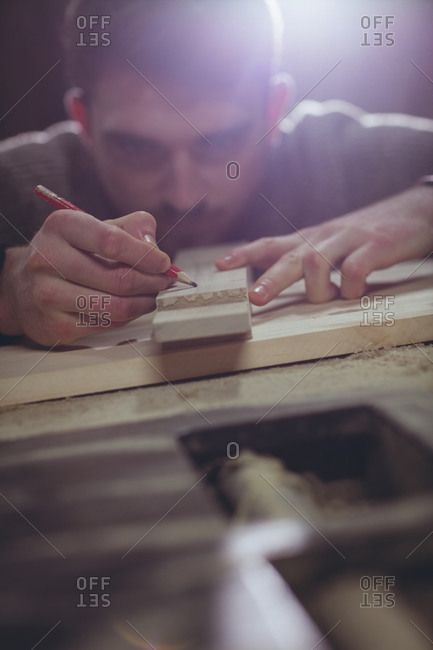 Carpenter making notes in a woodshop