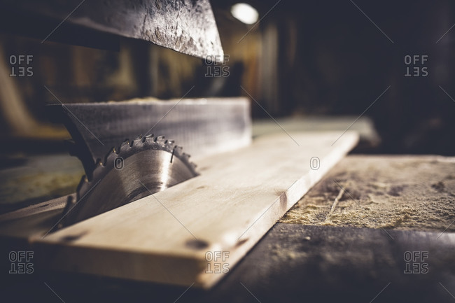 Saw sawing plank of wood in a dusty workshop