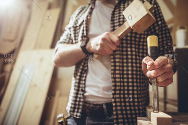 Carpenter using a hammer in a workshop