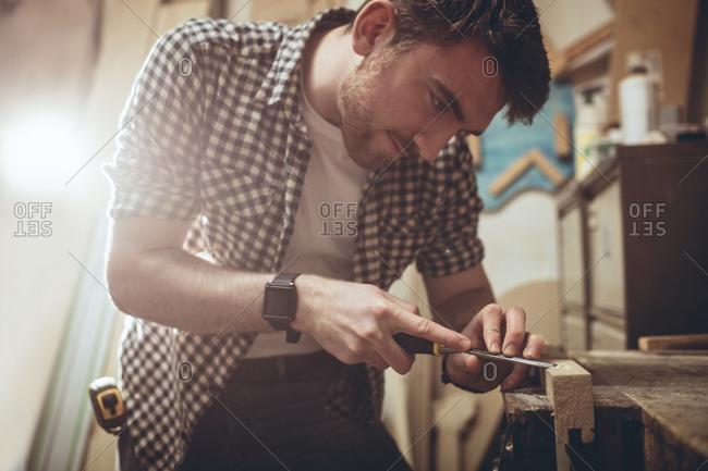 Carpenter using a chisel in a workshop