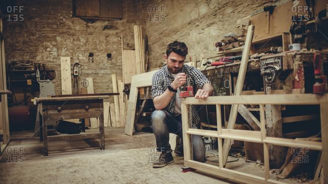 Carpenter assembling wood project in his studio