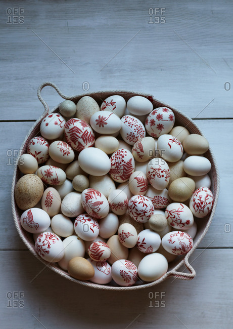 Easter eggs with red designs in a round basket