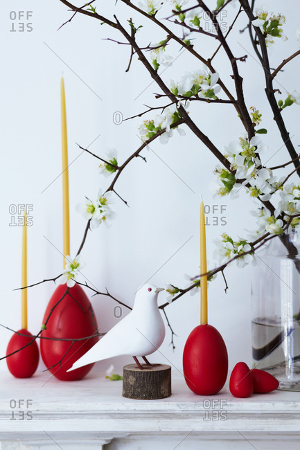 Egg candleholders and a branch in bloom decorating a mantelpiece