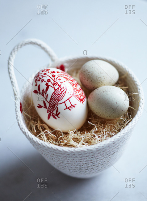 Easter eggs in a small woven basket with straw