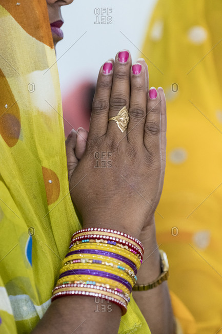 Hands of a praying woman at a Christian service in India
