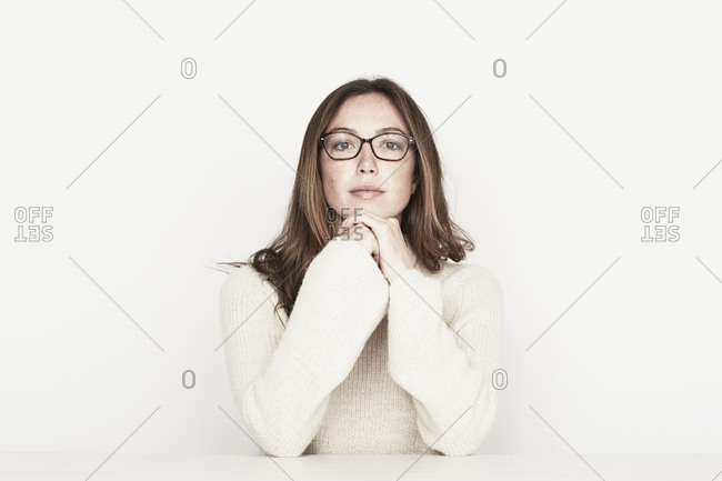 Young woman in glasses resting chin in hands