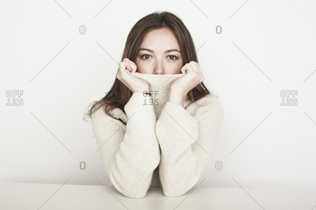 Female covering mouth with turtleneck