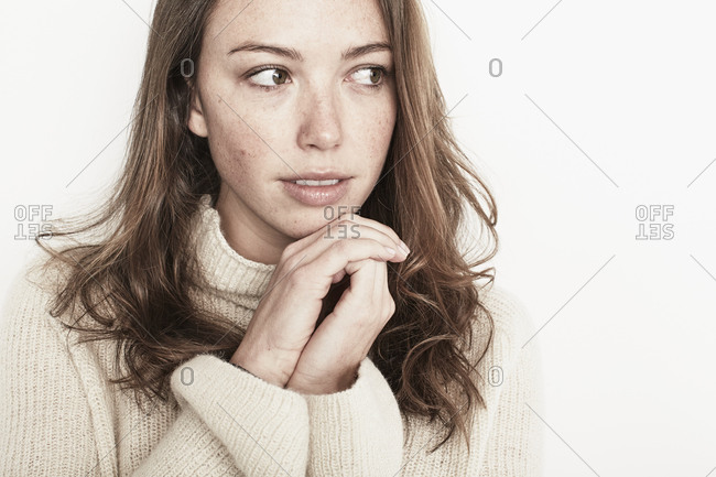 Young woman with freckles resting chin on clasp hands